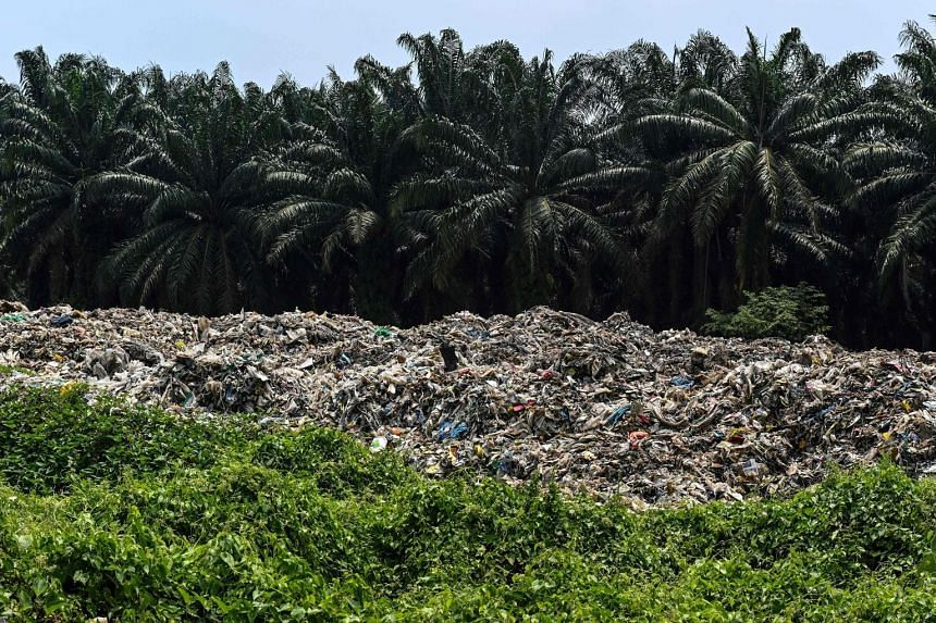 Plastic waste near palm oil trees at an abandoned factory in Jenjarom, a district of Kuala Langat, outside Kuala Lumpur. In Malaysia, huge amounts of imported plastic waste have ended up being dumped in the countryside.
