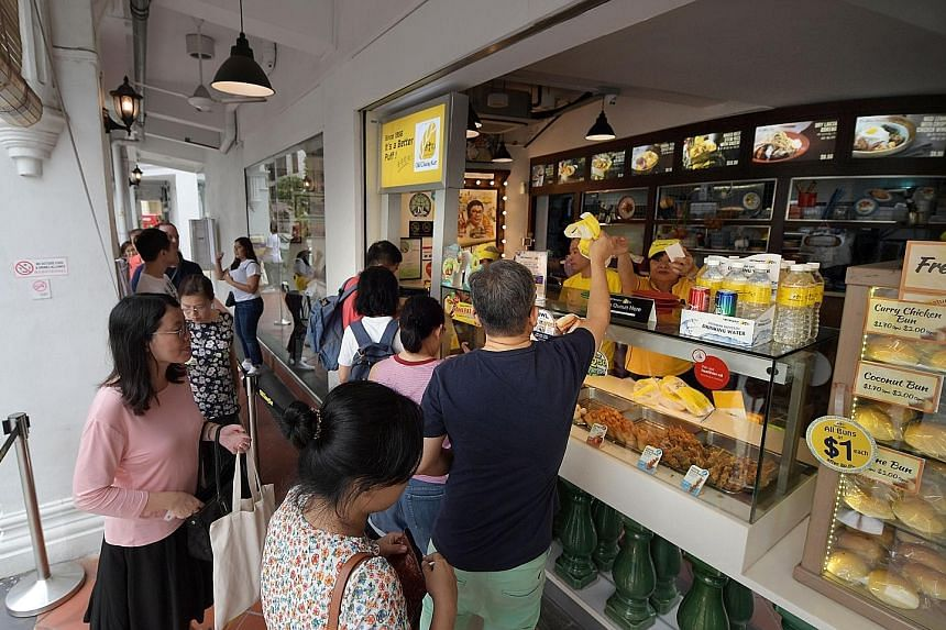 A steady stream of SPH direct subscribers redeeming their curry puffs at the Old Chang Kee Coffee House @ Rex yesterday.