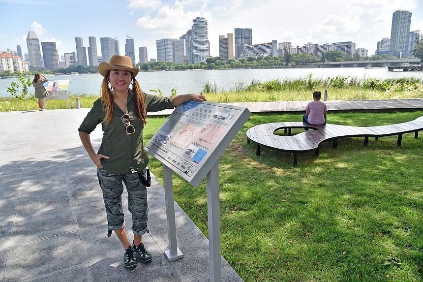 "The heritage trail's project manager Teresa Teo Guttensohn next to a trail marker, ""Of Stilts and Cheroots"", and a Re:Bench, one of 14 functional artworks made from the timber seats of the old National Stadium."