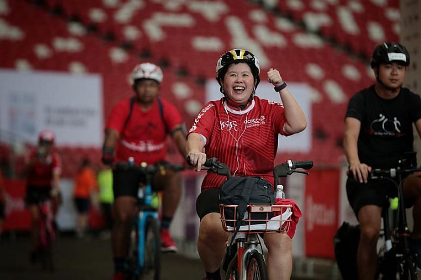 Cyclists react as they cross the finish line during the OCBC Cycle 2019 on May 12, 2019.