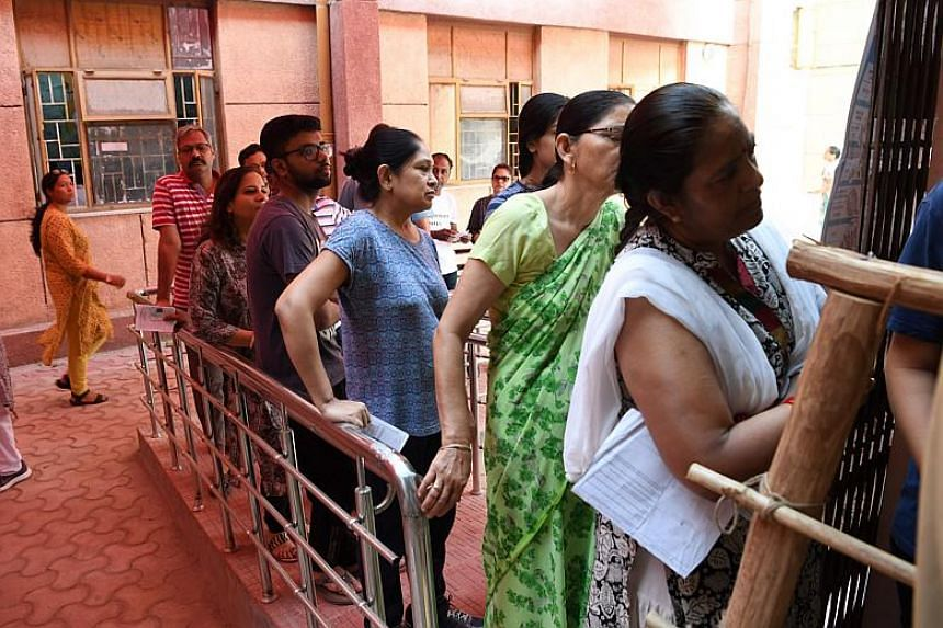 People queue up to cast their votes at a polling station in the sixth phase of India's general election, in New Delhi on May 12, 2019.