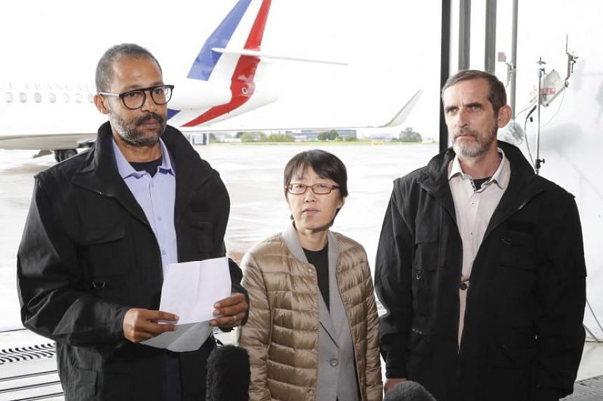 Freed French hostages Patrick Picque (right) and Laurent Lassimouillas (left) stand next to a South Korean hostage as they talk to the press upon their arrival at the Villacoublay airport, near Paris, France, on May 11, 2019.