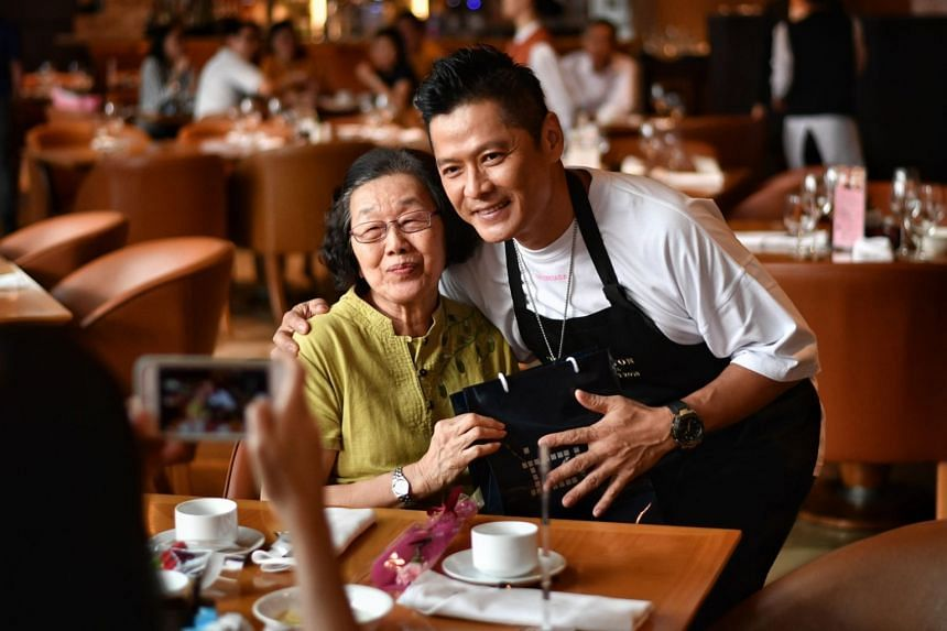 Li Nanxing taking a picture with retiree Mdm Patricia Lee, 75, who was there with her daughter and a friend.