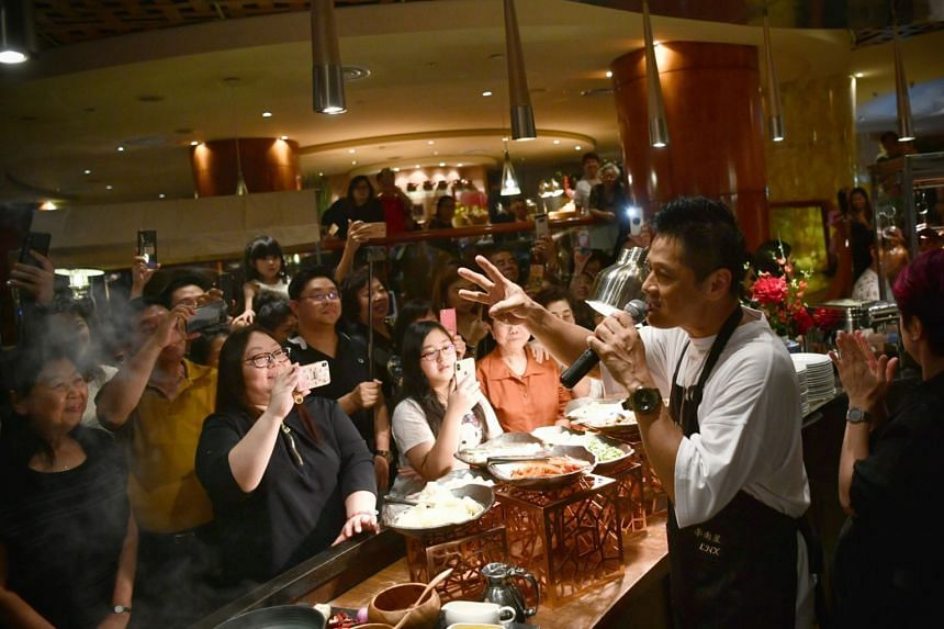 Li Nanxing speaking to excited patrons over a microphone at The Fullerton Hotel.