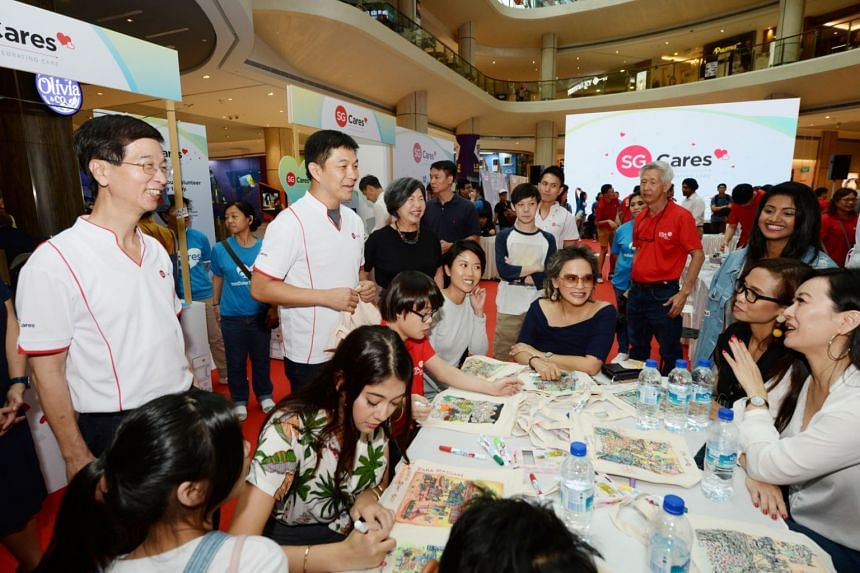 """Speaker of Parliament Tan Chuan-Jin (second from left) interacting with participants of the SG Cares """"Celebrating Our Culture of Care"""" event at Suntec City."""