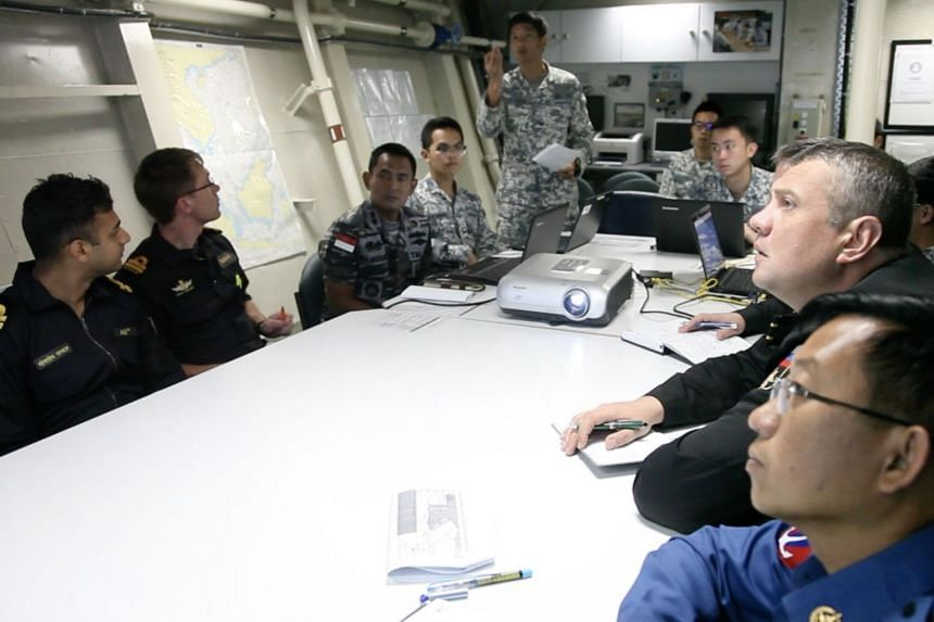 Participants of the ADMM-Plus Maritime Security Field Training Exercise exchanging information with the Information Fusion Centre in Singapore to locate vessels of interest.
