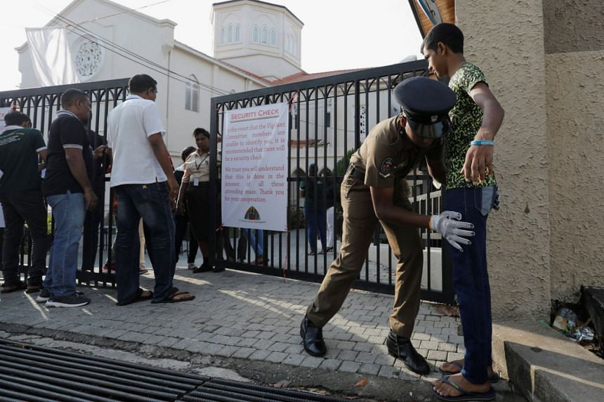 A police officer searches a worshipper at the main entrance of St Theresa's church as the Catholic churches in Sri Lanka restart their Sunday services in Colombo, Sri Lanka, on May 12, 2019.