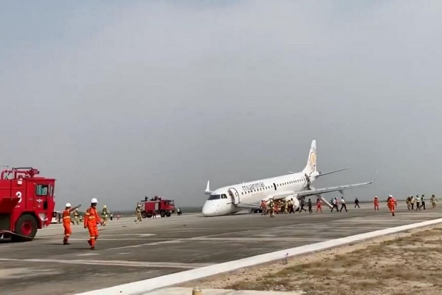 A passenger records the scene on her phone as firefighters attend to the scene after Myanmar National Airlines flight UB103 landed without a front wheel at Mandalay International Airport in Tada-U, Myanmar.