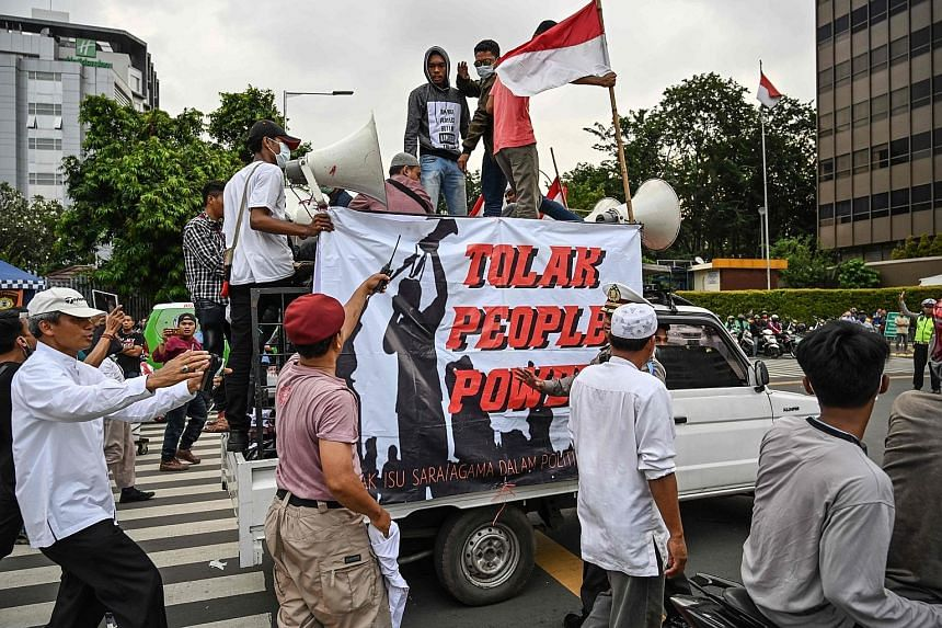 Members of the Islam Defenders Front and supporters of presidential candidate Prabowo Subianto confronting a group on the back of a pick-up truck supporting the General Elections Commission - tasked with counting the ballots of the recent Indonesian