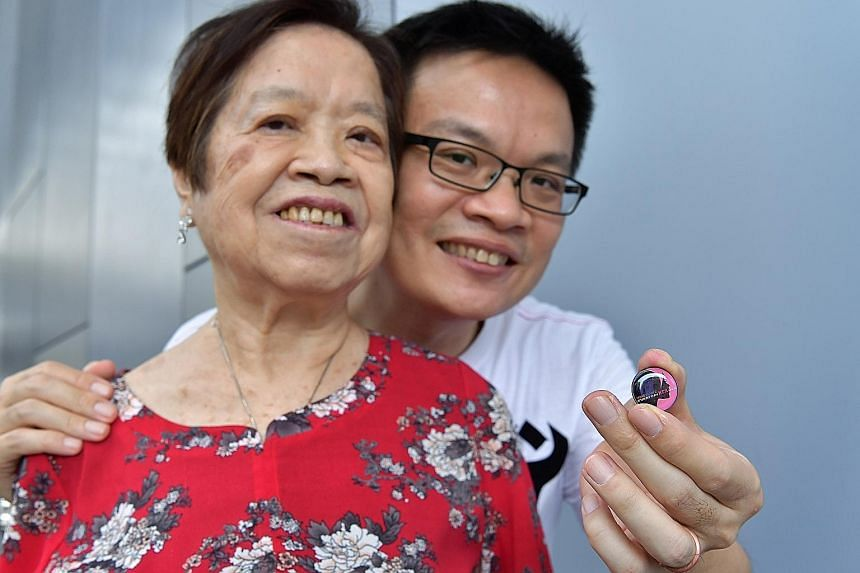 Police NSman and HomeTeamNS volunteer Jenson Goh, 45, with his 73-year-old mother Cheng Song Eng. The collar pin was given to her at the event at Our Tampines Hub yesterday.