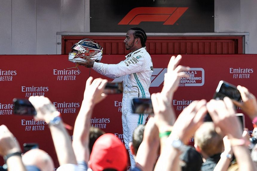 Mercedes' British driver Lewis Hamilton celebrating his Spanish Grand Prix victory yesterday. His fastest lap in the race also earned him an extra point.