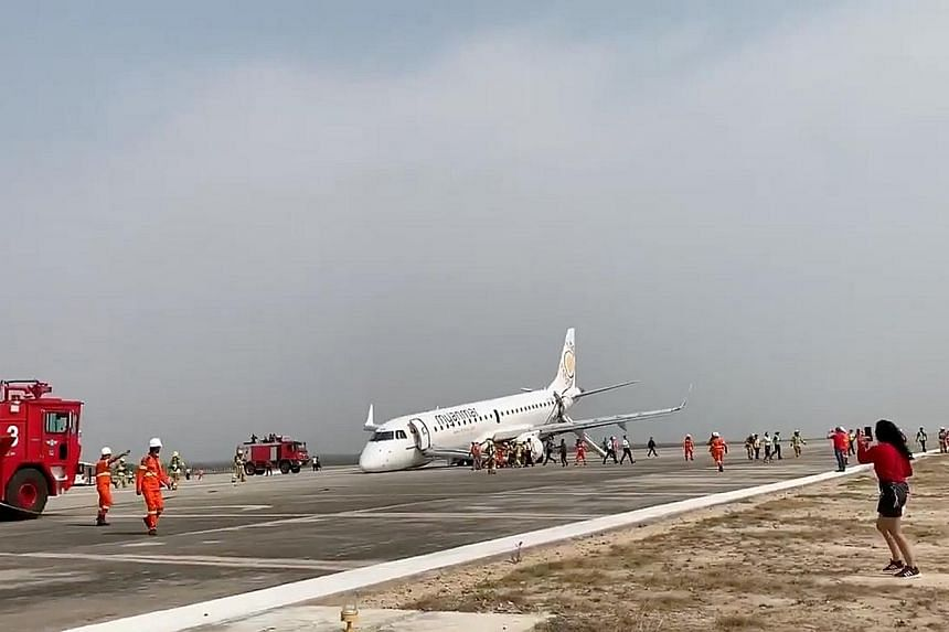 Firefighters at the scene after Myanmar National Airlines Flight UB103 made an emergency landing at Mandalay International Airport yesterday without its front wheels. Smoke entered the cabin (below) as passengers awaited evacuation.