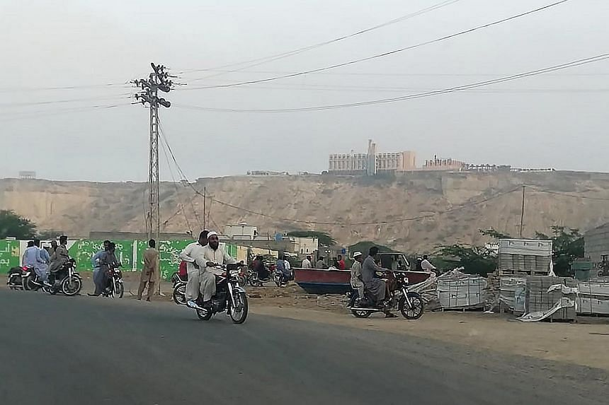 Pakistanis looking at the five-star Pearl Continental hotel sitting on a hill in the distance in the south-western Pakistani city of Gwadar last Saturday, when three gunmen raided the hotel and killed five people.