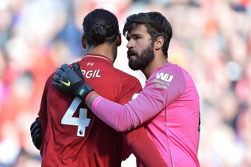 Defender Virgil van Dijk (left), PFA Player of the Year, getting a pat from Golden Glove winner Alisson after Liverpool beat Wolves 2-0 at Anfield yesterday. There were personal accolades aplenty for the Reds but no trophy. PHOTO: EPA-EFE