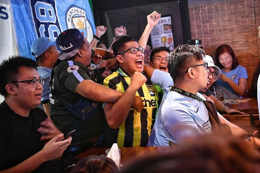 Left: Manchester City fans cheering their team on against Brighton at Thunderbird Sports Bistro. ST PHOTO: ARIFFIN JAMAR Below: Fans celebrating their team's first goal against Wolves during the official Liverpool Supporters Club in Singapore screeni