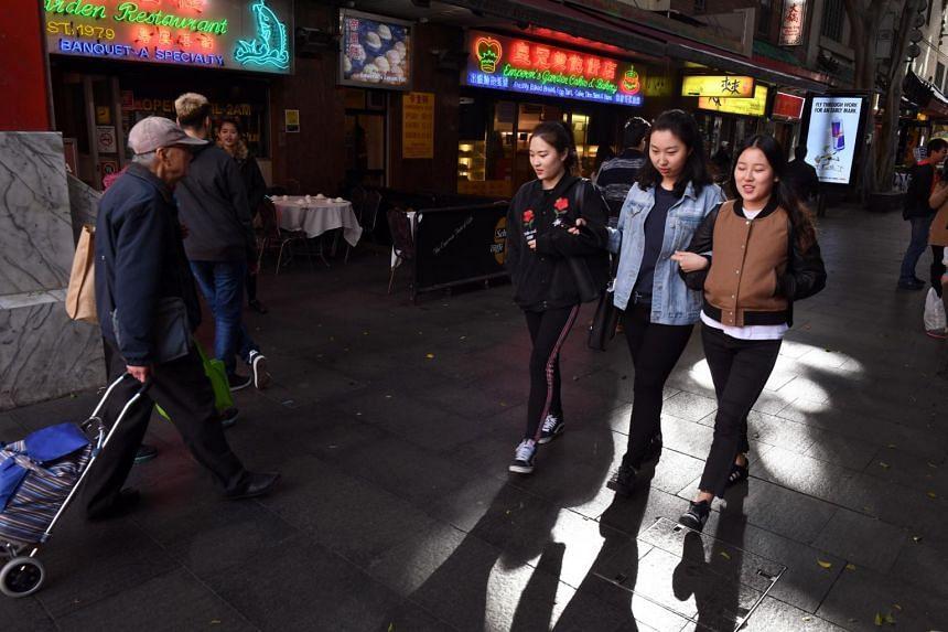 People walk through Sydney's Chinatown, on June 21, 2017.