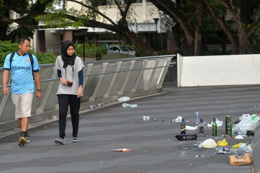Passers-by looking at some litter left on the Alexandra Arch bridge along Henderson Road.