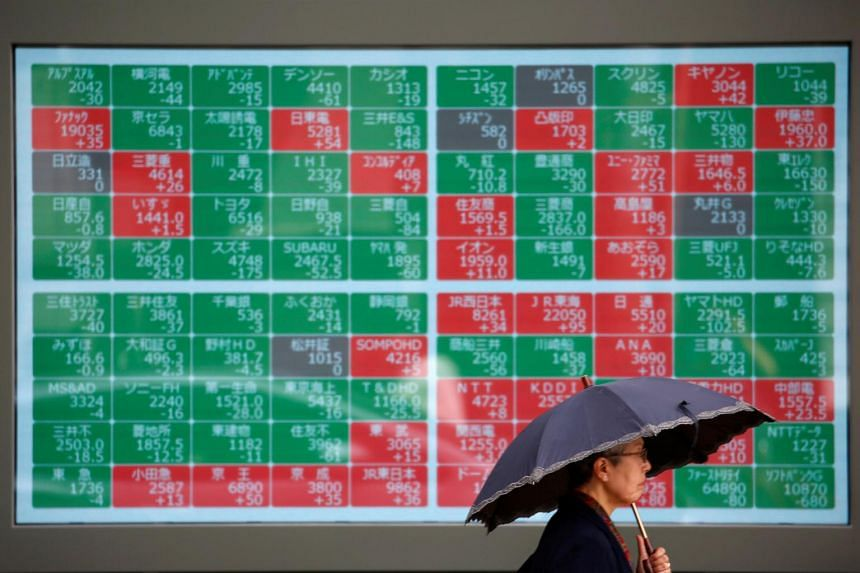 A passer-by walks past in front of a stock quotation board outside a brokerage in Tokyo, Japan.