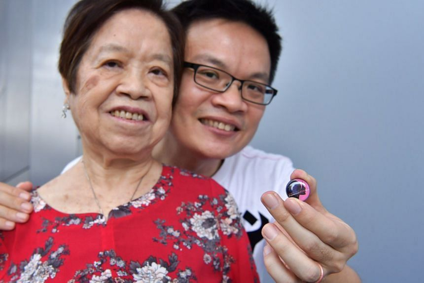 Police NSman and HomeTeamNS volunteer, Jenson Goh Chong Leng with his mother, Cheng Song Eng, 73, and the collar pin for wives and mothers of NSmen in recognition of their contributions to national service.