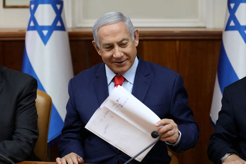 Israeli Prime Minister Benjamin Netanyahu holds a paper at the start of the weekly cabinet meeting at his Jerusalem office May 12, 2019.