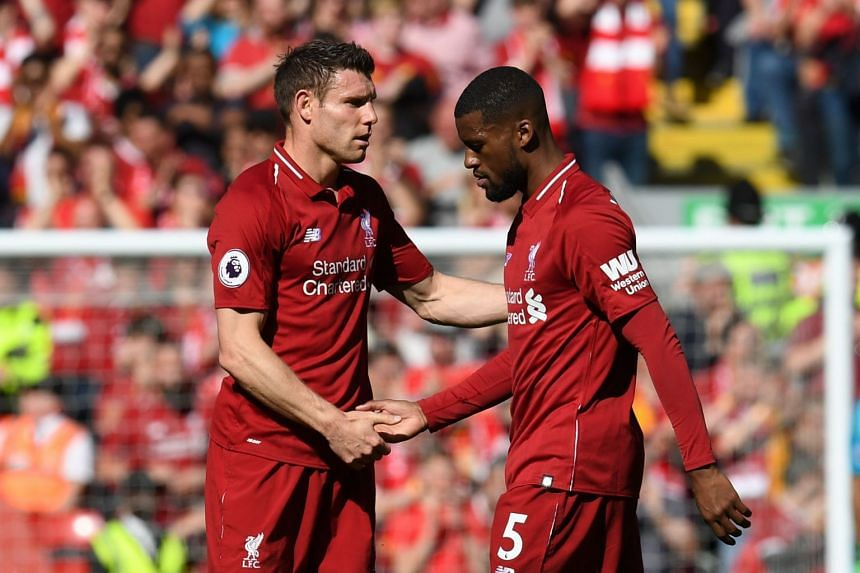 Liverpool's English midfielder James Milner (lef) shakes hands with Liverpool's Dutch midfielder Georginio Wijnaldum at the end of the English Premier League football match between Liverpool and Wolverhampton Wanderers at Anfield in Liverpool, north-