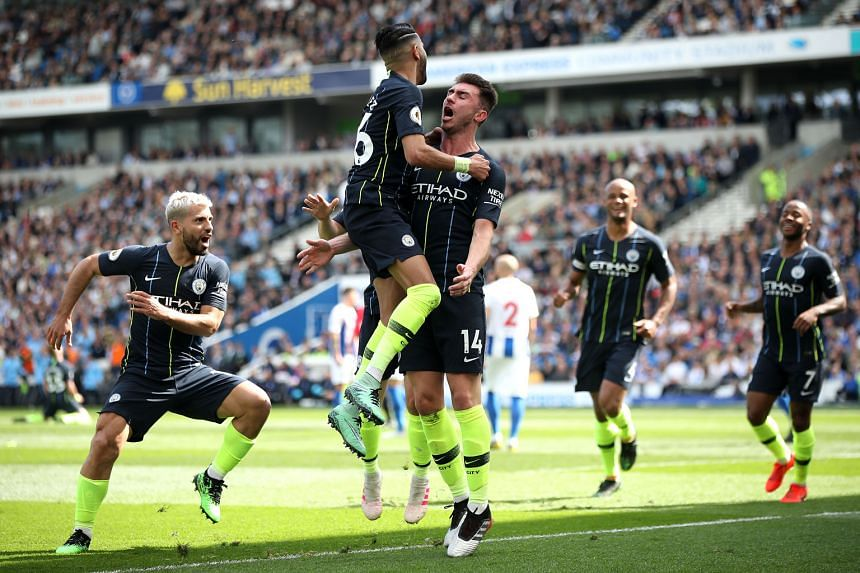 Aymeric Laporte (third from left) celebrating the all-important second goal that put Manchester City 2-1 up at Brighton, after the champions had conceded a shock opener at the Amex Stadium yesterday.