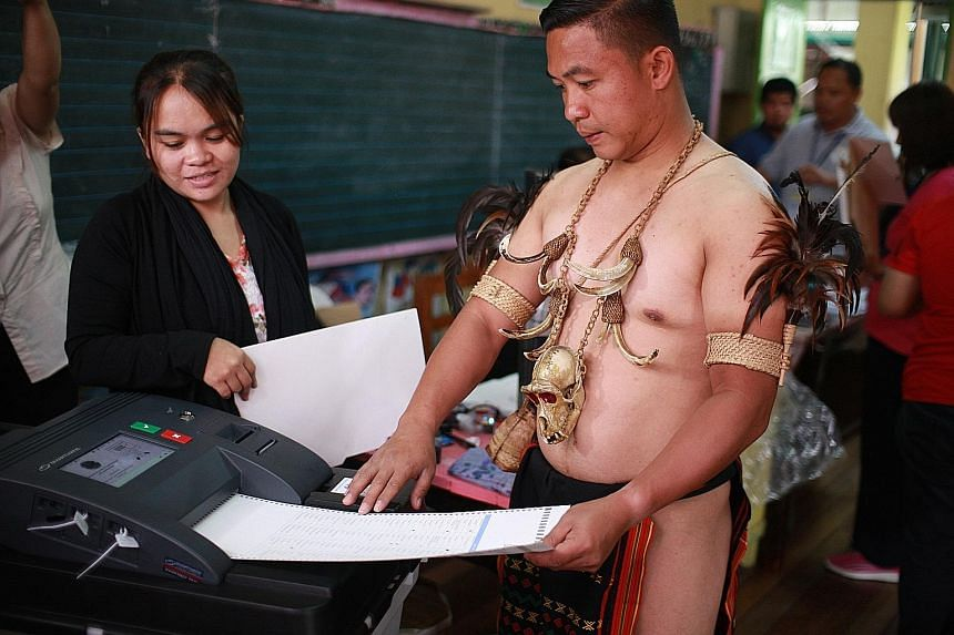 A member of the Filipino indigenous Igorot tribe casting his ballot yesterday at a polling station in Baguio City, in the northern Philippines.