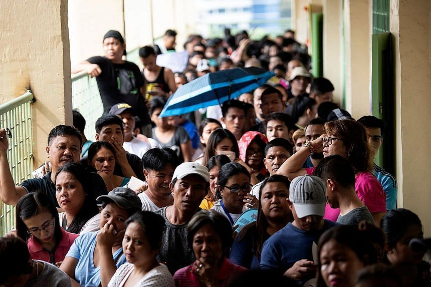 Filipinos waiting to vote at Culiat Elementary School in Manila yesterday. The midterm polls are expected to strengthen President Rodrigo Duterte's grip on power, opening the way for him to deliver on pledges to restore the death penalty and rewrite