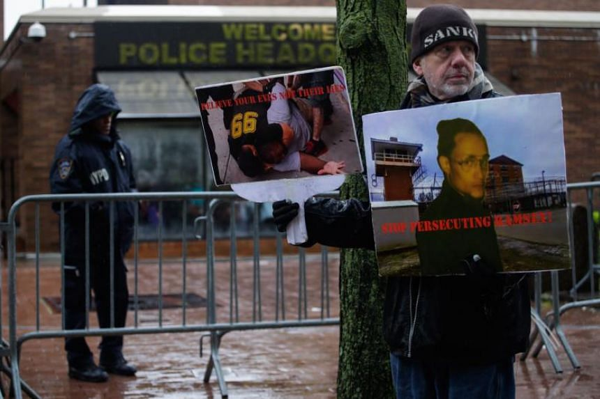 A man holds a poster showing an image of Eric Garner outside police headquarters as a disciplinary hearing takes place for officer Daniel Pantaleo on May 13, 2019, in New York City.