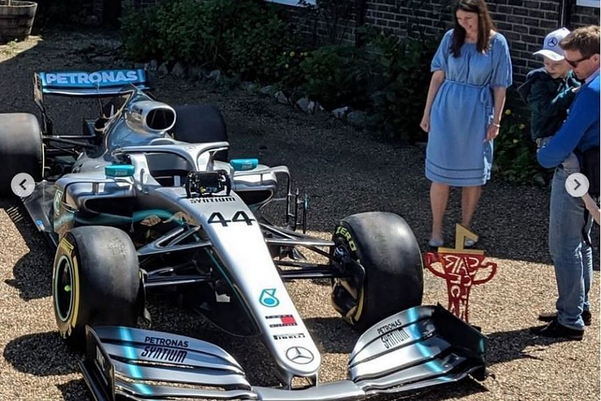 Five-year-old Harry Shaw, cradled in his father James' arms, was shown around Lewis Hamilton's car by a Mercedes employee.