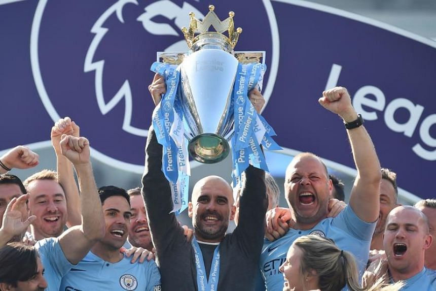 Manchester City's Spanish manager, Pep Guardiola, holds up the Premier League trophy as he's surrounded by his team after their 4-1 victory in the English Premier League football match between Brighton and Hove Albion and Manchester City at the Ameri