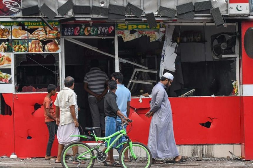 Passers-by at a badly damaged shop after a mob attack in Minuwangoda, Sri Lanka, on May 14, 2019.