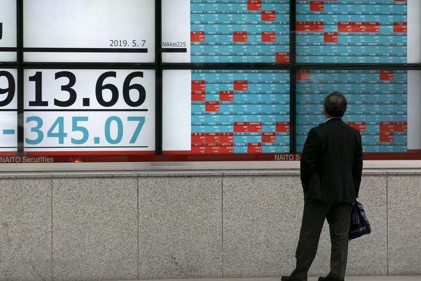 A pedestrian looking at a display showing the Tokyo stock index at a securities office in Tokyo, Japan, on May 7, 2019.