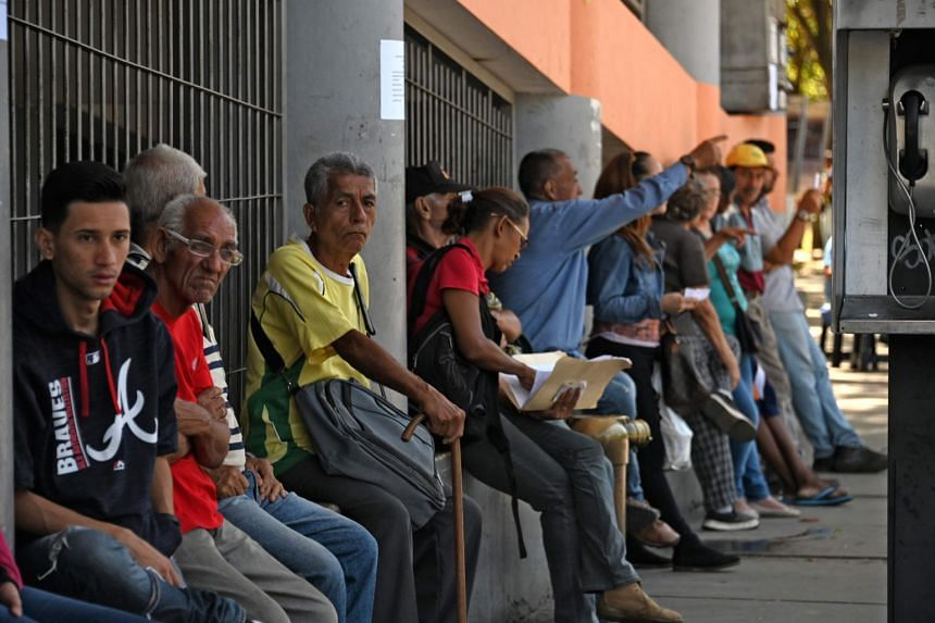 Venezuelans sit outside a hospital in Caracas on May 13, 2019. The country is suffering from serious shortages of basic necessities such as food and medicine after five years of recession.