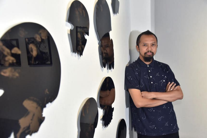 Repeat, Repeat, Repeat: Revising The Phenomenon Of Printing guest curator Zaki Razak with Miguel Chew's jellyfish-shaped prints, with a partial view of Yeo Shih Yun's Impossibility Of Repetition in the reflection.
