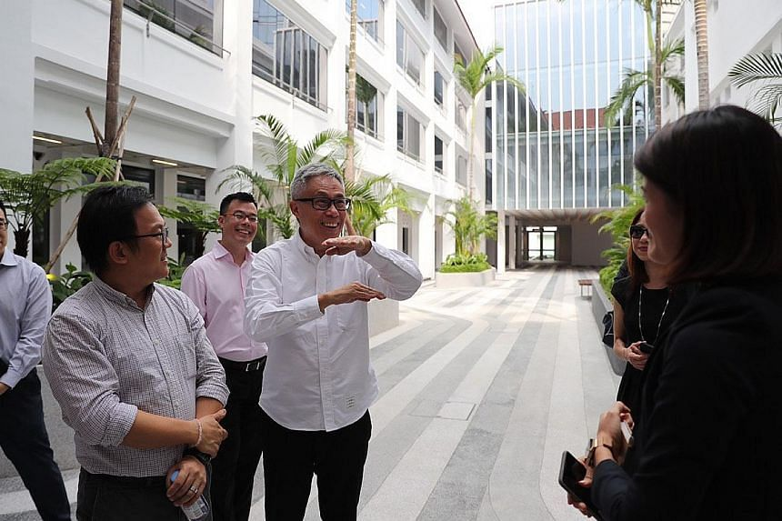 Far left: (From left) Mr Ho Weng Hin, Mr Han Kok Juan and Mr Mok Wei Wei in one of the building's courtyards. Refurbishment work included reinstating the neutral tones of the building facade (above) and constructing an overhead link bridge (left).