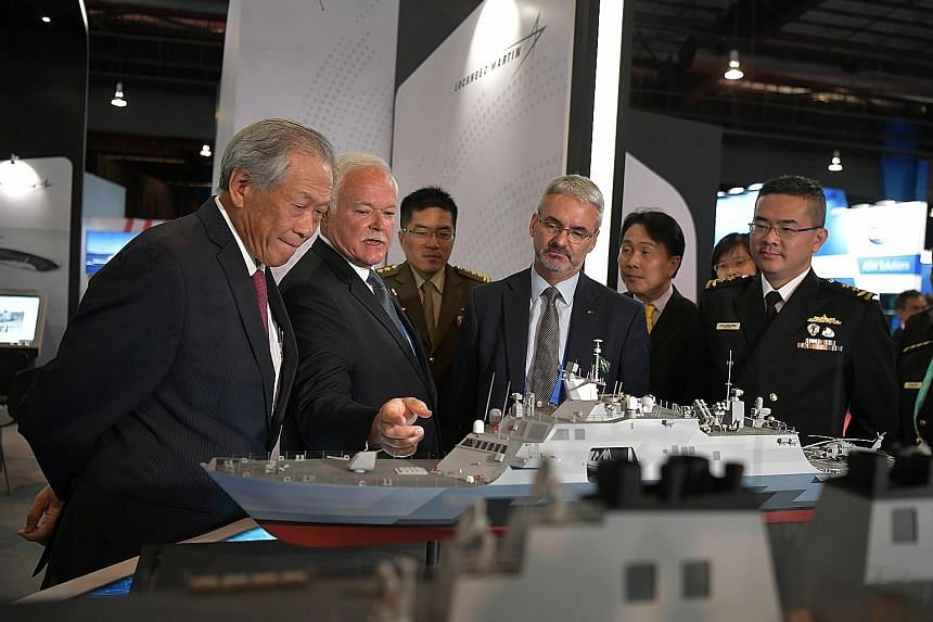 Defence Minister Ng Eng Hen (left), Chief of Defence Force Melvyn Ong (third from left) and Chief of Navy Lew Chuen Hong (right) visiting the Lockheed Martin booth yesterday at the 12th International Maritime Defence Exhibition and Conference Asia. S
