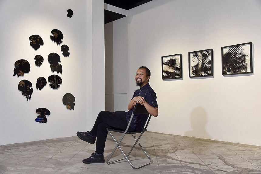 Repeat, Repeat, Repeat: Revising The Phenomenon Of Printing curator Zaki Razak is seen here with Miguel Chew's Beauty Lie On The Eye Of The Beholder 1.1 (far left) and Yeo Shih Yun's Impossibility Of Repetition (left).