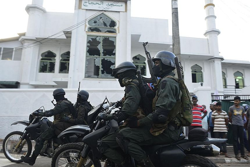 Heavily-armed Sri Lankan soldiers riding past the Jumha Mosque after a mob attack in Minuwangoda yesterday. A curfew is in place in the country's North-Western Province, where attackers set fire to Muslim-owned shops, vandalised homes and smashed win