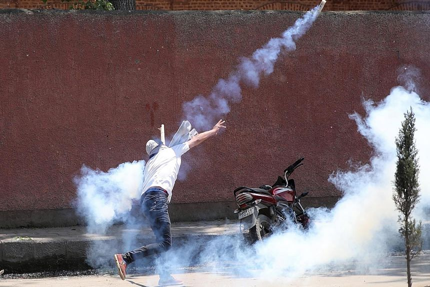 A Kashmiri student throwing back a tear smoke shell at Indian police during clashes in Srinagar yesterday over the rape of a child. Thousands of students protested for a second day across many towns in the region, calling for the accused to be given