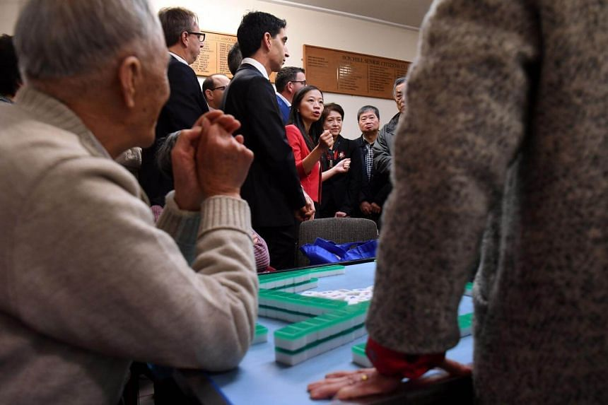 Elderly Chinese-Australians at a club take a break from mahjong to listen to Labor Party candidate Jennifer Yang (centre, in red) on May 9, 2019. She will run in an election for Chisholm, Melbourne, where one in five households speaks either Mandarin