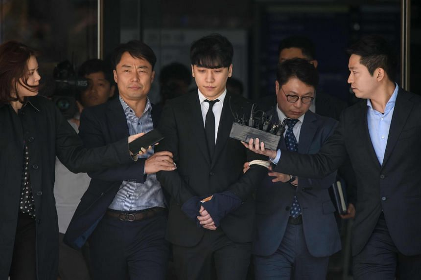 Former BigBang singer Seungri (centre) is taken into custody as he leaves the High Court in Seoul on May 14, 2019.