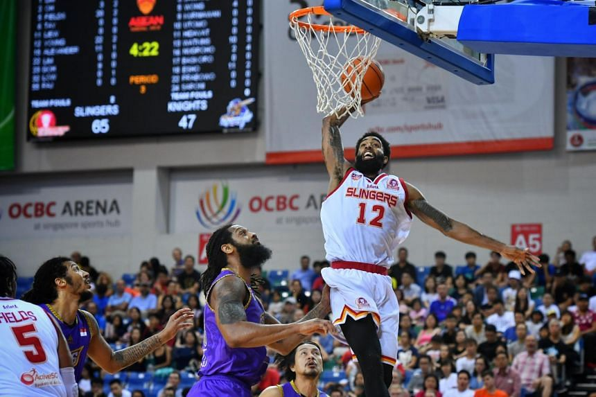Singapore Slinger's Jerran Young (right, no.12) scores in the Asean Basketball League match between the Singapore Slingers vs CLS Knights Indonesia held at OCBC Arena, on Feb 3, 2019.