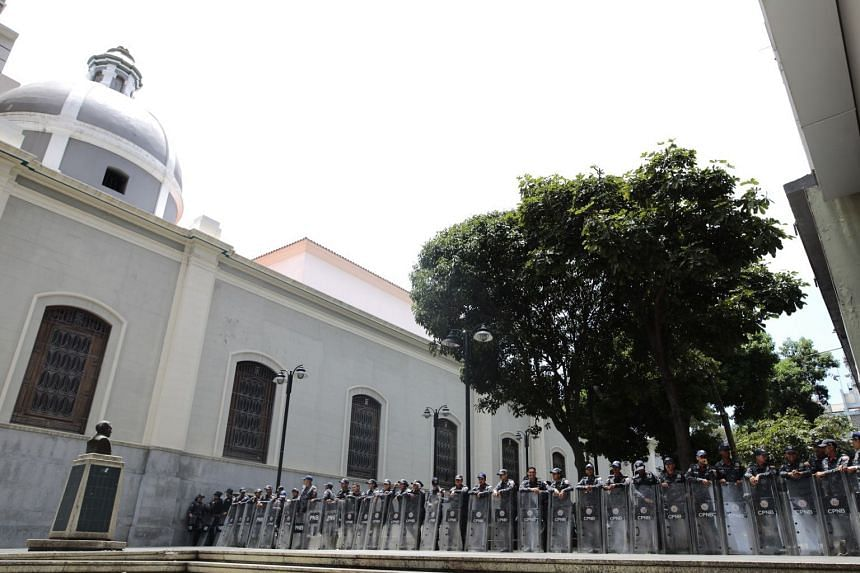 Policemen block the way to the opposition-controlled National Assembly of Venezuela during a search operation for an explosive device inside the building.