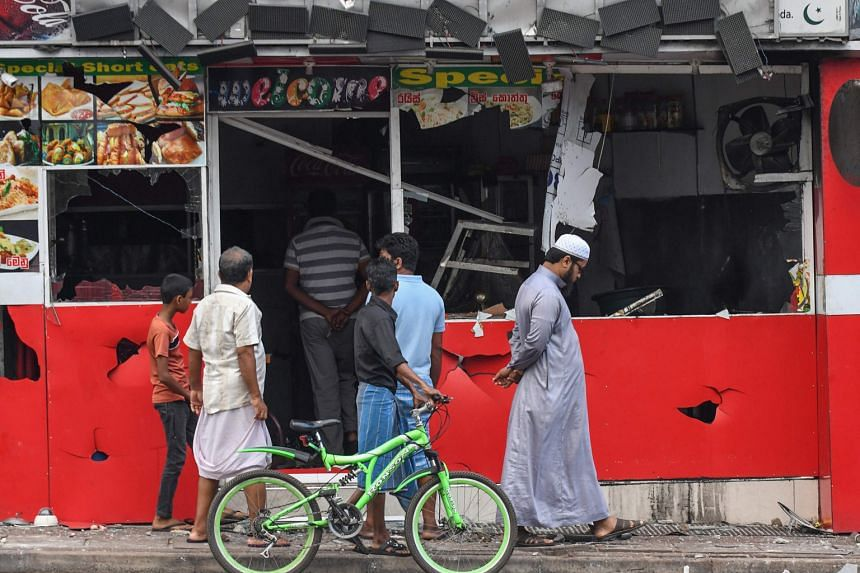 People viewing a damaged shop yesterday after an anti-Muslim mob attack in Minuwangoda, Sri Lanka. PHOTO: AGENCE FRANCE-PRESSE