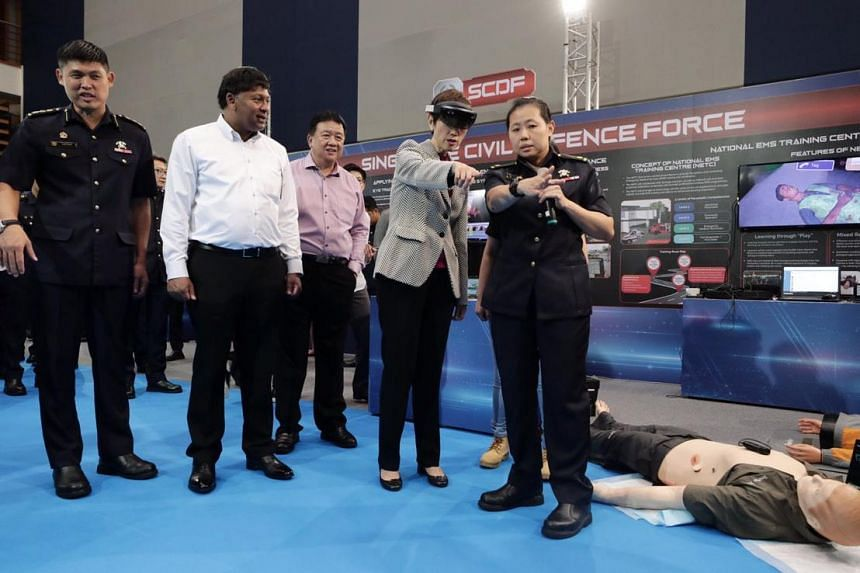 Minister for Manpower and Second Minister for Home Affairs Josephine Teo (second from right) trying the hololens at SCDF event booth with guidance from Major Carolyn Low (far right).