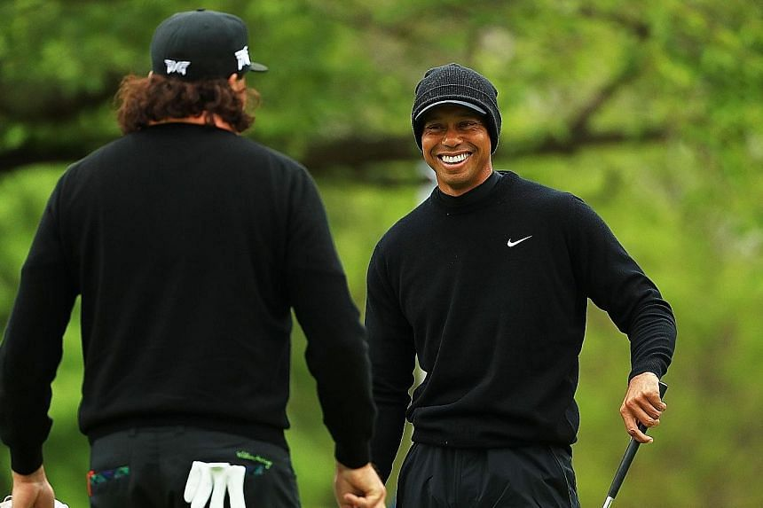 Tiger Woods chatting with American compatriot Pat Perez during a practice round ahead of the PGA Championship at Bethpage Black on Tuesday. This will be Woods' first tournament since his Masters victory a month ago. PHOTO: AGENCE FRANCE-PRESSE