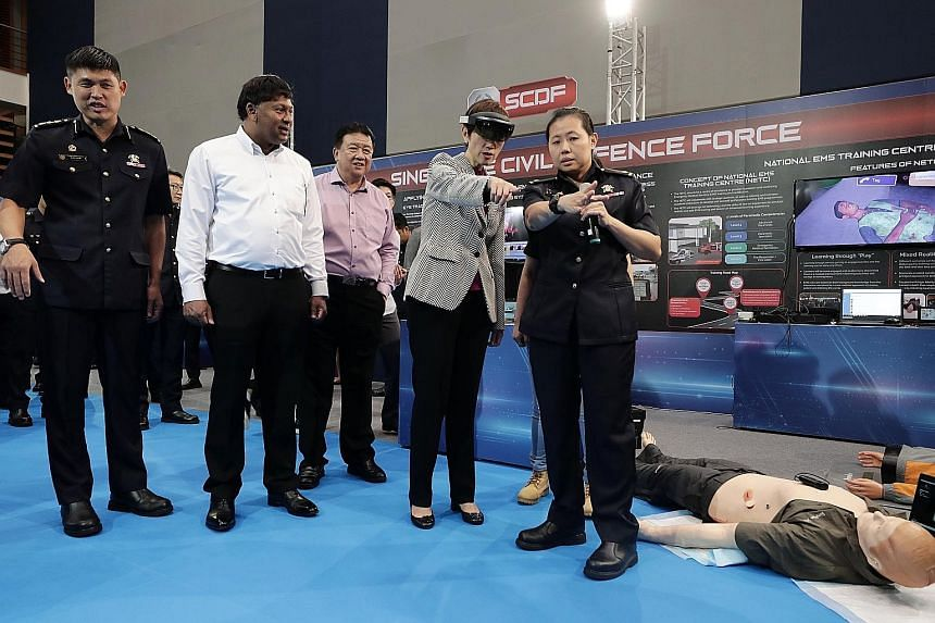 Below: Minister Josephine Teo trying out the hololens under Major Low's guidance, observed by (from left) CDA director Alan Chow, Ministry of Home Affairs Deputy Secretary T. Raja Kumar and Home Team Academy chief executive Clarence Yeo. Left: Singap