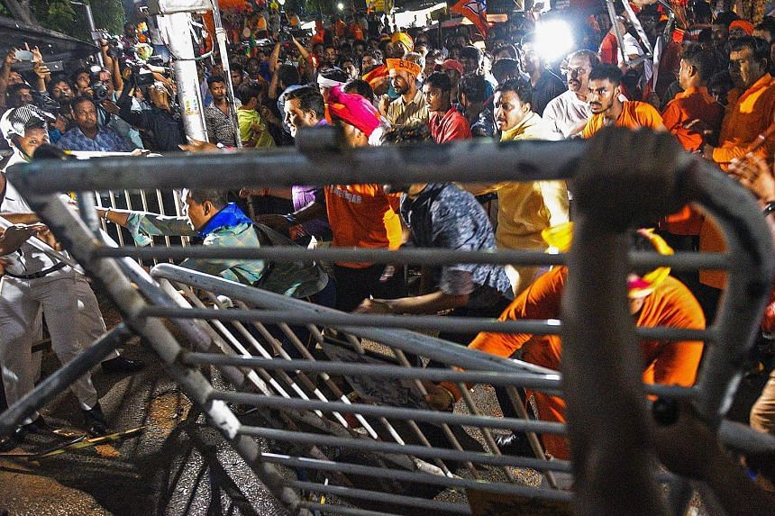 BJP supporters facing off Indian police amid clashes between rival groups during a campaign rally event held by BJP president Amit Shah in Kolkata on Tuesday. Fifty-nine people were arrested in the street battles.