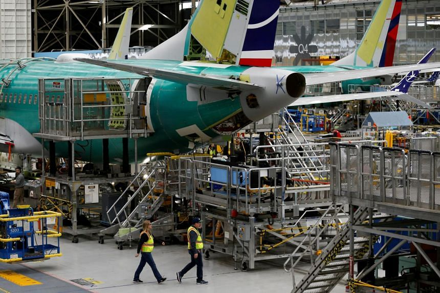 Employees walk by the end of a 737 Max aircraft at the Boeing factory in Renton, Washington, on March 27, 2019.